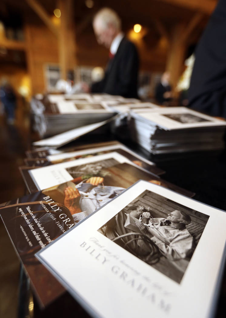 A stack of remembrance brochures are placed at the entrance as people come to pay respects to Billy Graham during a public viewing at the Billy Graham Library in Charlotte, N.C., Monday, Feb. 26,  ...