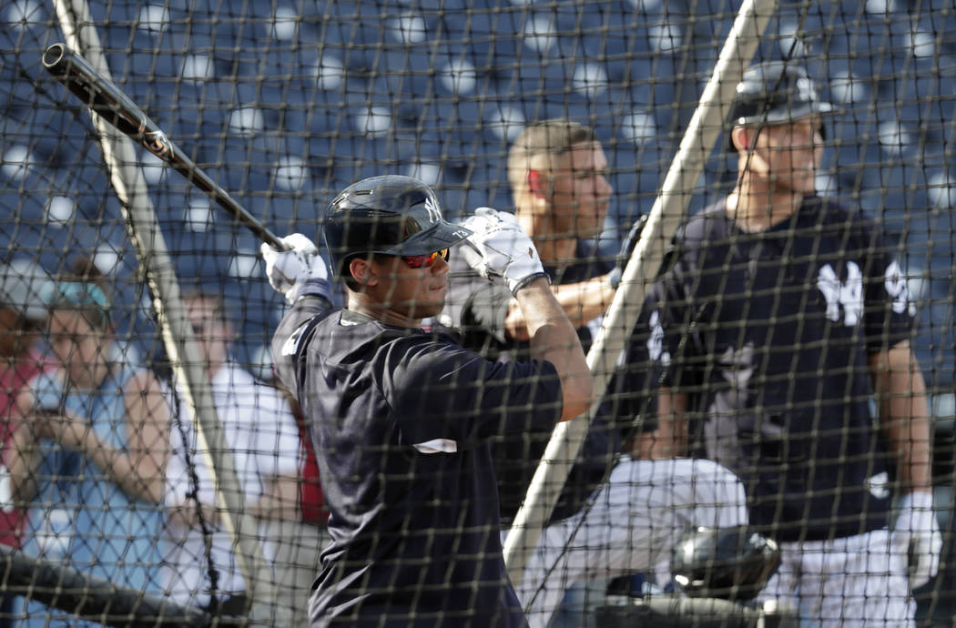 Seattle Seahawks quarterback Russell Wilson, center, hits during batting practice as Aaron Judge, right, looks on before a baseball spring exhibition game against the Philadelphia Phillies, Monday ...