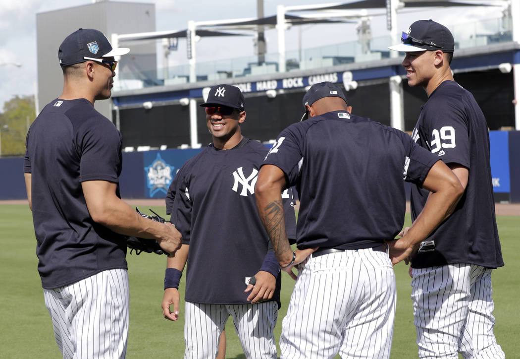 Seattle Seahawks quarterback Russell Wilson, second from left, talks with New York Yankees' Giancarlo Stanton, left, and Aaron Judge (99) before a baseball spring exhibition game against the Phila ...