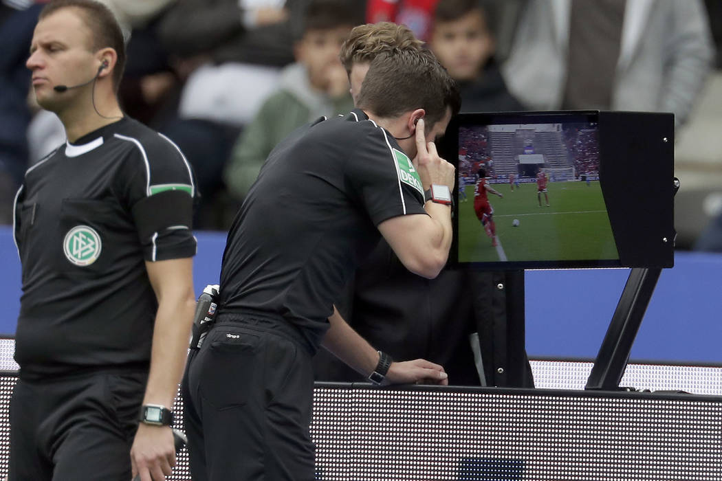 In this Sunday, Oct. 1, 2017 file photo, referee Harm Osmers looks at a video screen to decide whether to give a penalty against Bayern Munich during the German Bundesliga soccer match between Her ...