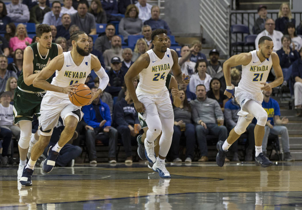 Nevada's Cody Martin, left, leads a fast break against Colorado State in the first half of an NCAA college basketball game in Reno, Nev., Sunday, Feb. 25, 2018. (AP Photo/Tom R. Smedes)