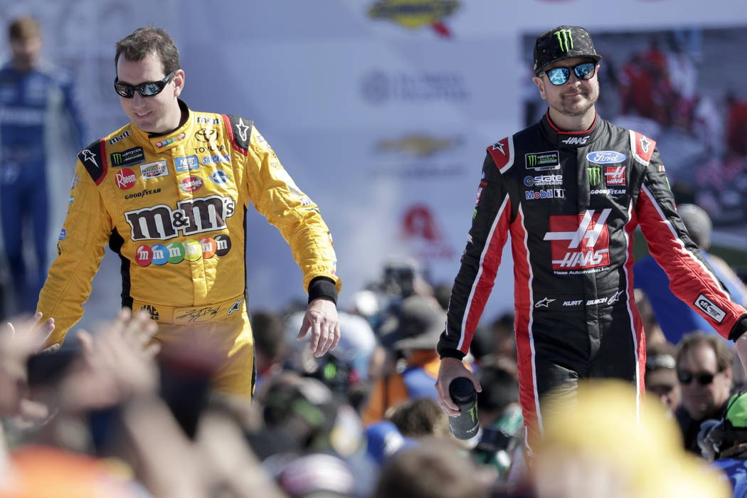 Kyle Busch, left, and Kurt Busch, right, greet fans as they are introduced before the NASCAR Daytona 500 Cup series auto race at Daytona International Speedway in Daytona Beach, Fla., Sunday, Feb. ...