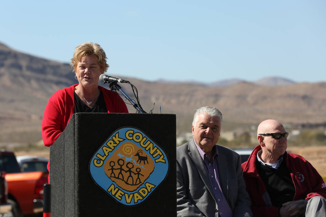Clark County commissioners Larry Brown, right, and Steve Sisolak listen as Mindy Meyers, Acting Director of Clark County Parks and Recreation, speaks to a crowd during the groundbreaking ceremony  ...