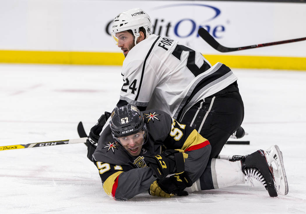 Vegas Golden Knights left wing David Perron (57) and Los Angeles Kings defenseman Derek Forbort (24) get tripped up over each other during the first period of an NHL hockey game at T-Mobile Arena  ...