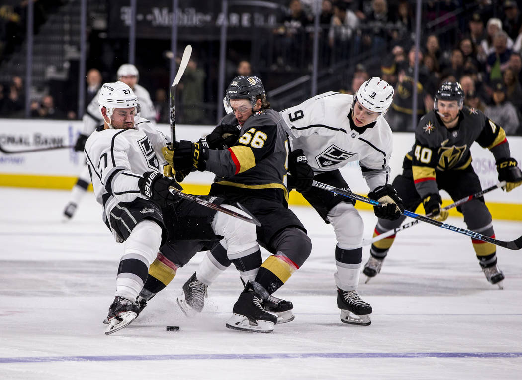 Los Angeles Kings defenseman Alec Martinez (27) and Vegas Golden Knights left wing Erik Haula (56) get tangled up while chasing the puck during the first period of an NHL hockey game at T-Mobile A ...