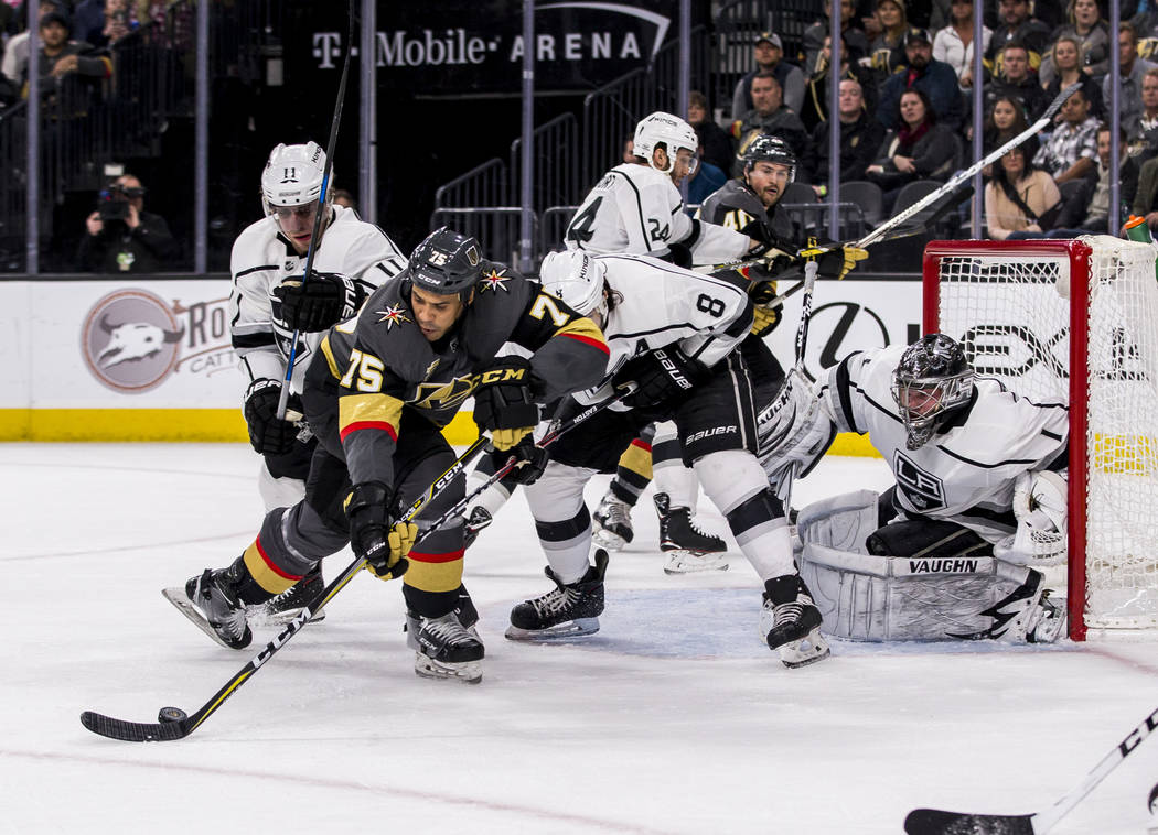 Vegas Golden Knights right wing Ryan Reaves (75) tries to get the puck away from Los Angeles Kings center Anze Kopitar (11) and Los Angeles Kings defenseman Drew Doughty (8) during the first perio ...