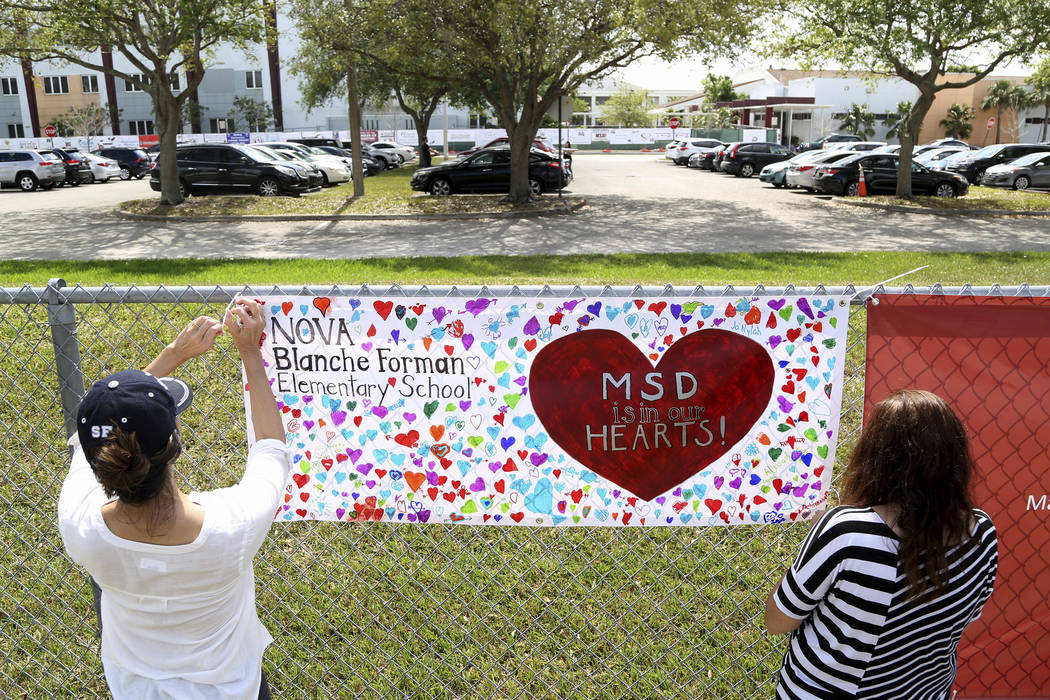 Volunteers hang banners around the perimeter of Marjory Stoneman High School in Parkland, Fla., to welcome back students who will be returning to school Wednesday two weeks after the mass shooting ...