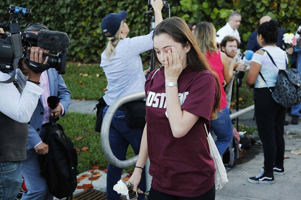A student walks past the media at Marjory Stoneman Douglas High School in Parkland, Fla., Wednesday, Feb. 28, 2018. Students returned to class for the first time since 17 people were killed on Feb ...