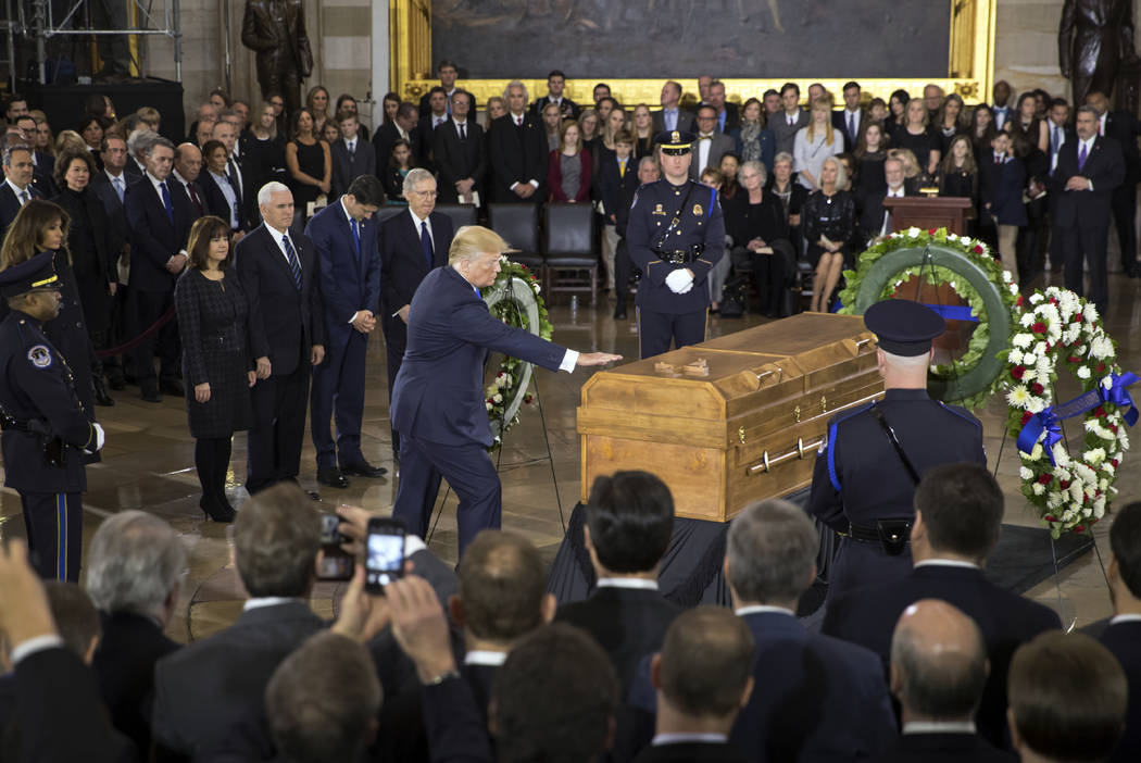 President Donald Trump touches the casket of Rev. Billy Graham, who died last week at age 99, during a ceremony in the Capitol Rotunda where he will lie in honor as a tribute to America's most fam ...