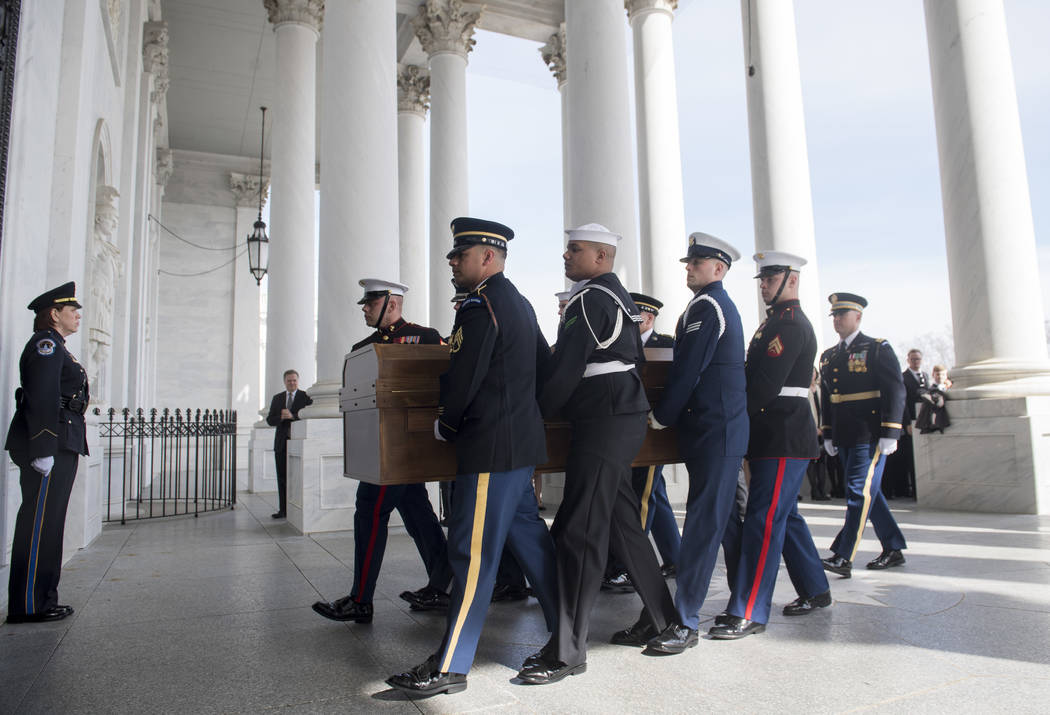 A Military Honor Guard carries the casket of Reverend Billy Graham as it arrives at the US Capitol in Washington, Feb. 28, 2018, prior to a lying in honor ceremony in the Capitol Rotunda. (Saul Lo ...