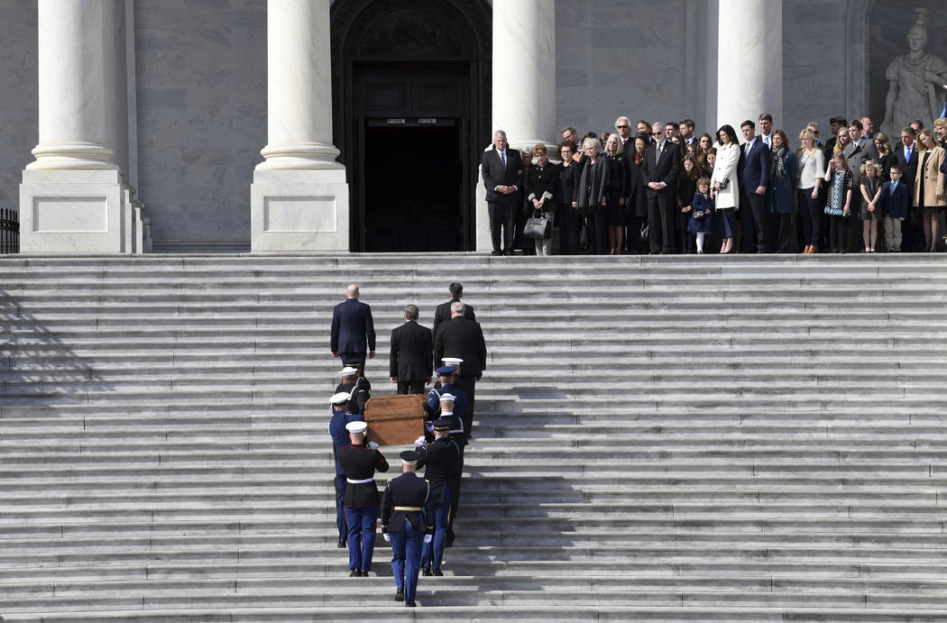 The family of Rev. Billy Graham watches as the casket of Rev. Billy Graham is carried up the steps of the U.S. Capitol in Washington, Wednesday, Feb. 28, 2018, where it will lie in honor in the Ro ...
