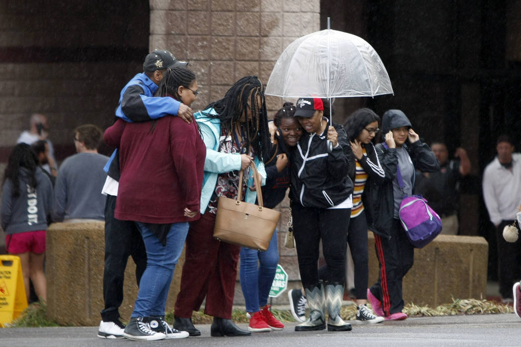 People hug one another outside of the Dalton Convention Center on Wednesday, Feb. 28, 2018 in Dalton, Ga. Students from Dalton High School were evacuated to the Dalton Convention Center after soci ...