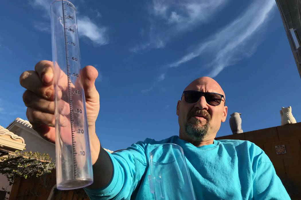 Volunteer rain spotter Scott Cereck­­­e shows off the precipitation gauge in the backyard of his Henderson home. He is part of an international network of weather observers that is looking to e ...