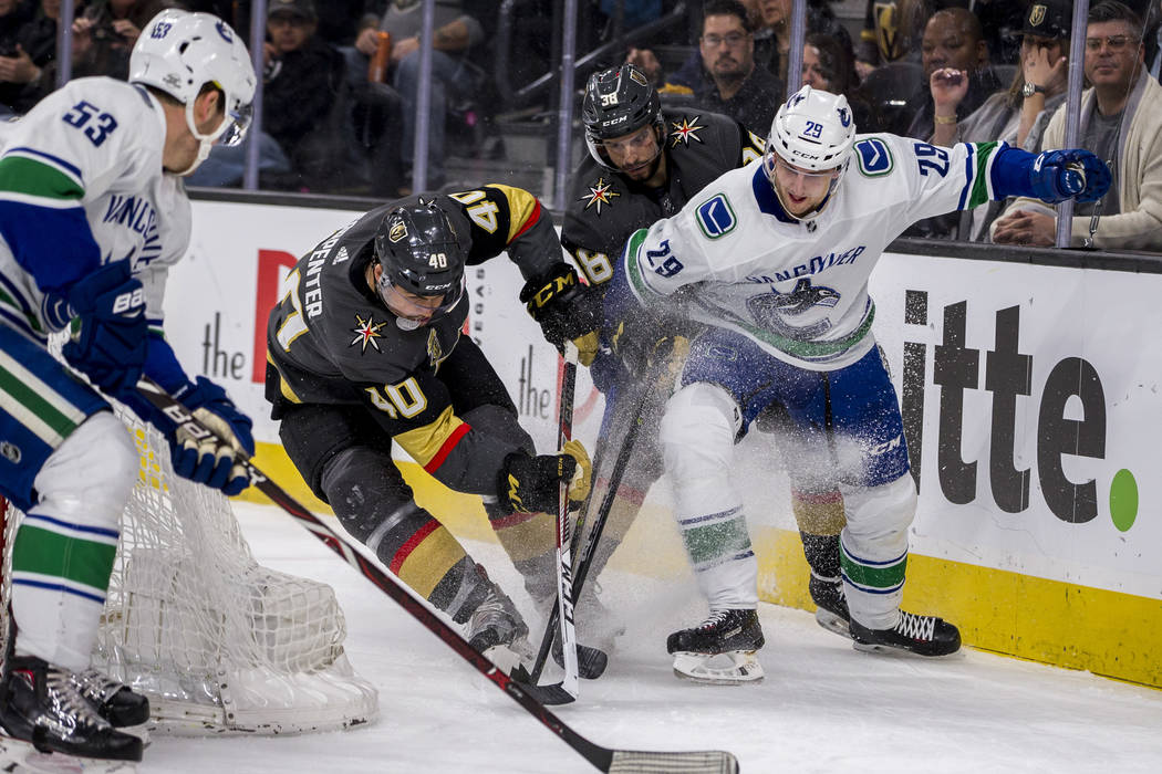 Golden Knights center Ryan Carpenter (40), Golden Knights right wing Tomas Hyka (38), Vancouver Canucks defenseman Philip Holm (29) and Vancouver Canucks center Bo Horvat (53) battle for the puck  ...