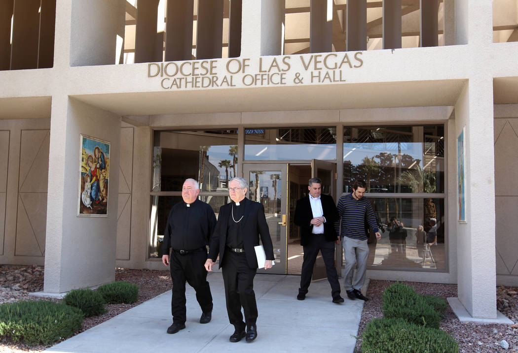 Bishop George Leo Thomas of the Diocese of Helena, second from left, after a news conference with the Rev. Robert Stoeckig, left, at the Diocese of Las Vegas Wednesday, Feb. 28, 2018, where he was ...