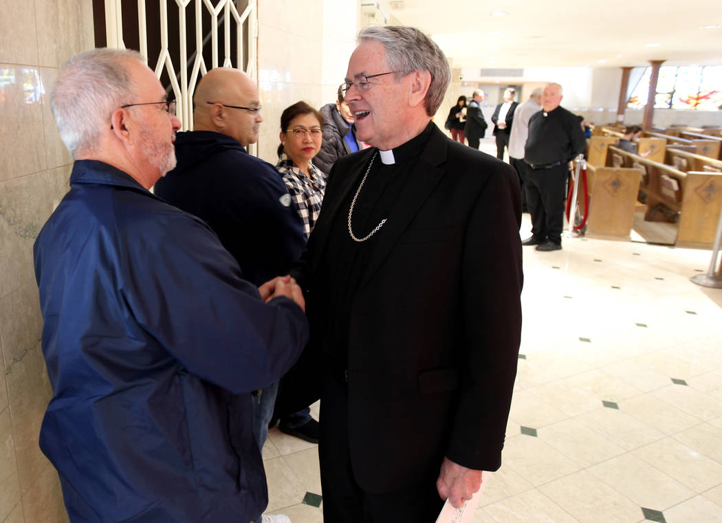 Bishop George Leo Thomas of the Diocese of Helena visits with John Ramos at Guardian Angel Cathedral Wednesday, Feb. 28, 2018, after he was introduced as the new bishop of the Roman Catholic Dioce ...