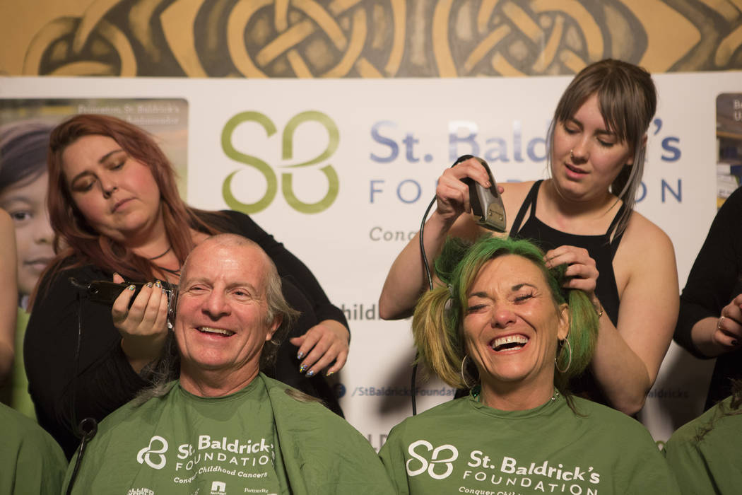 "Ben Haynie, left, and Kathy Haynie, right, get their heads shaved in part of ""Shave for the Cure"" a St. Baldrick's event held at McMullan's Irish Pub on Saturday, March 4, 2017, in Las V ..."