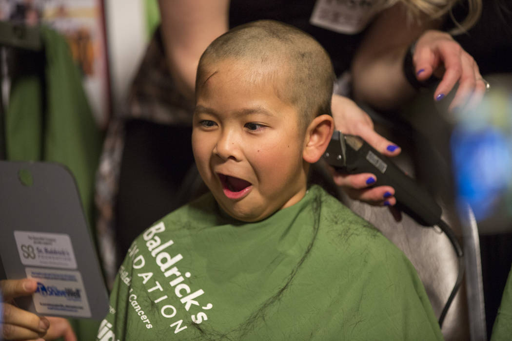 "Tayden Nguyen, 7, reacts to seeing his shaved head for the first time in part of ""Shave for the Cure"" a St. Baldrick's even at McMullan's Irish Pub on Saturday, March 4, 2017, in Las Veg ..."
