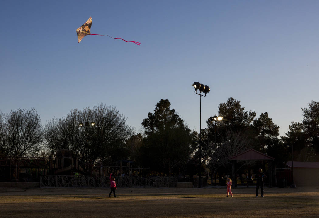 Las Vegas resident Chris Murray helps to fly kites with his daughter Arayah Murray, 5, center, and granddaughter Sydney Graham, 7, during a breezy late afternoon in Sunset Park in Las Vegas on Wed ...