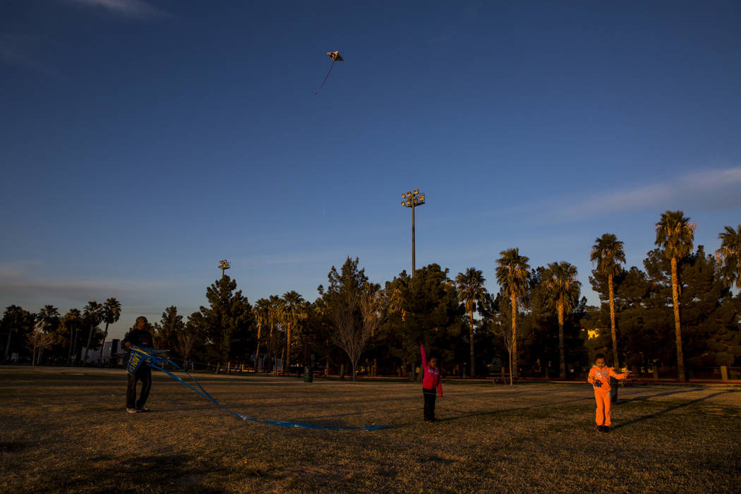 Las Vegas resident Chris Murray flies kites with his granddaughter Sydney Graham, 7, center, and daughter Arayah Murray, 5, during a breezy late afternoon in Sunset Park in Las Vegas on Wednesday, ...