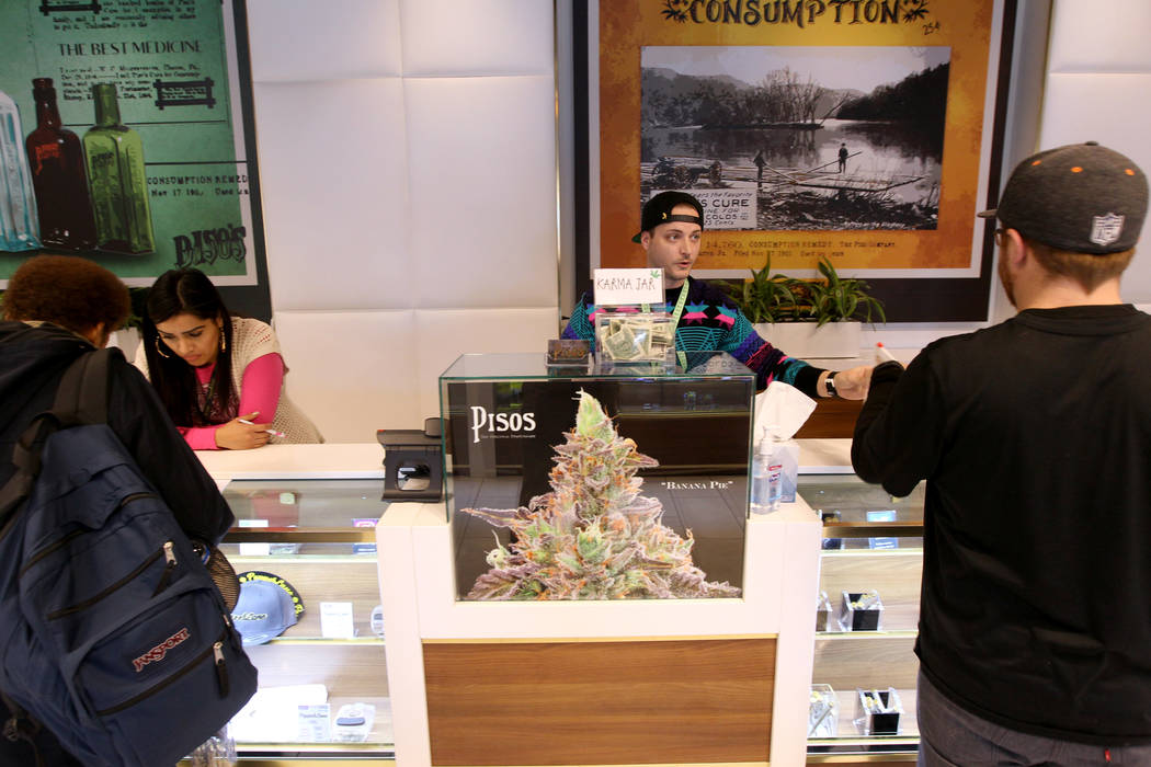 Budtender Patrick Murphy, center, gives a customer his product at Pisos dispensary, at 4110 S. Maryland Pkwy. in Las Vegas Monday, Jan. 22, 2018. Pisos is on the forefront of using cryptocurrency  ...