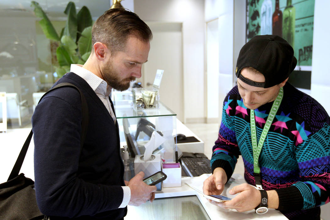 Gabriel Allred, co-founder of Tokes Platform, left, uses his cryptocurrency to make a purchase with budtender Patrick Murphy at Pisos dispensary, at 4110 S. Maryland Pkwy. in Las Vegas Monday, Jan ...