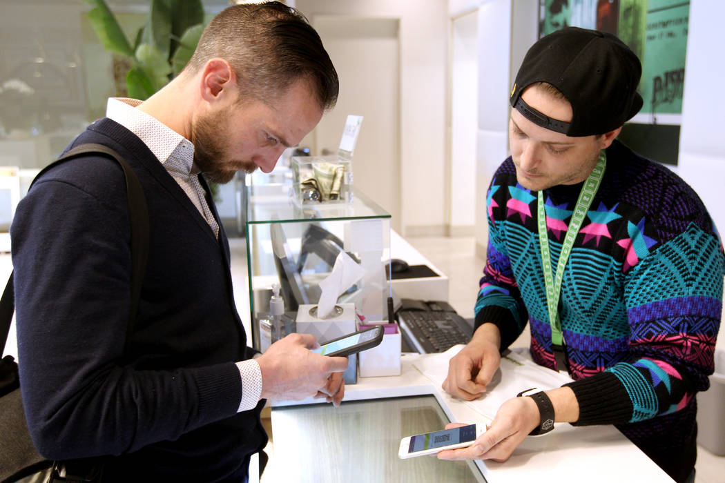 Gabriel Allred, co-founder of Tokes Platform, left, scans a QR bar code to use his cryptocurrency to make a purchase with budtender Patrick Murphy at Pisos dispensary, at 4110 S. Maryland Pkwy. in ...
