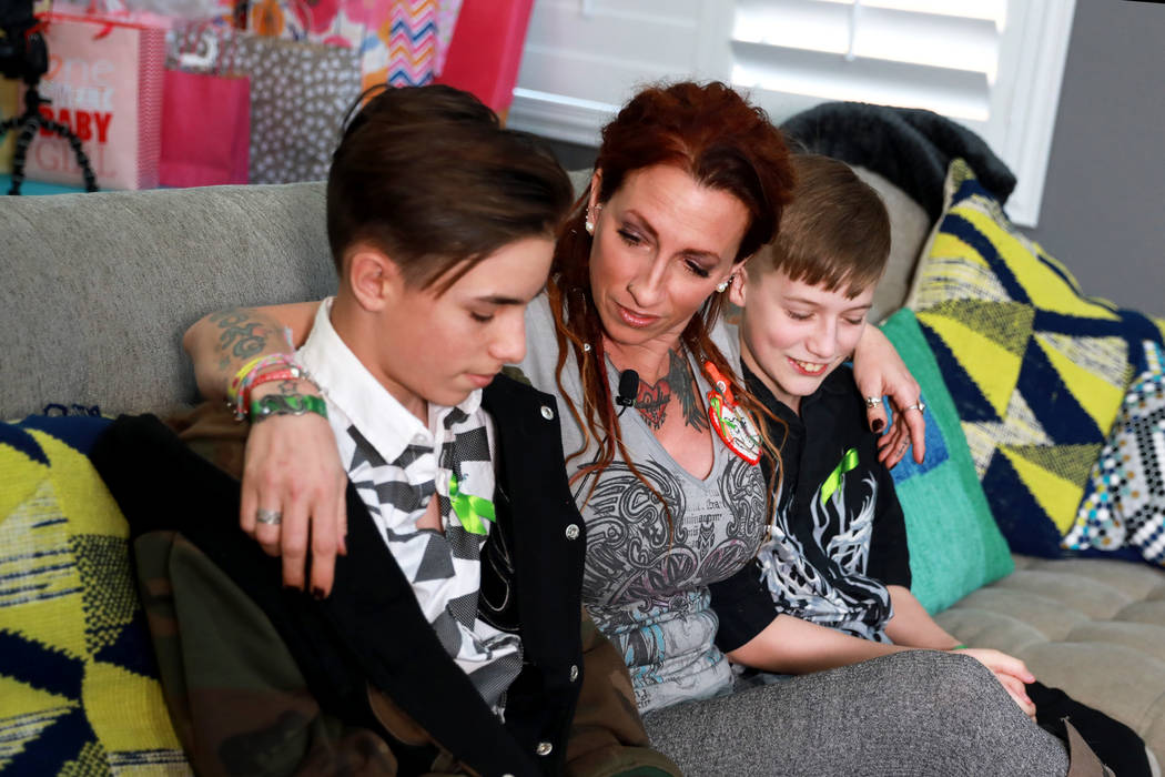 Las Vegas shooting survivor Mindy Foster, 42, with her sons Treydon Lapetina, 12, on her left, and Trenton Lapetina, 15, on her right. Foster discusses the impact of losing out on the pay she was  ...