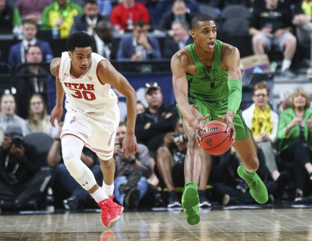 Oregon Ducks forward Kenny Wooten (1) regains control of a loose ball against Utah Utes guard Gabe Bealer (30) during the Pac-12 basketball tournament at T-Mobile Arena in Las Vegas on Thursday, M ...