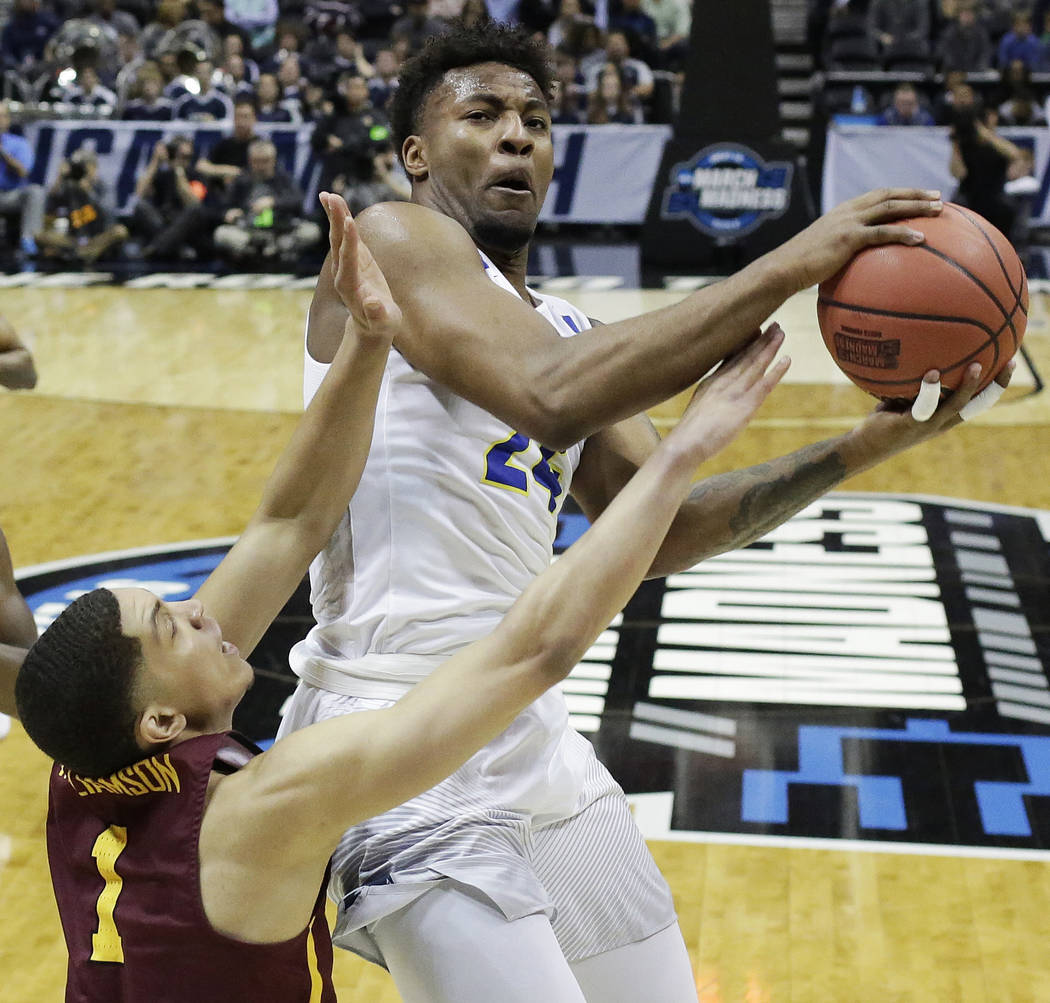 Nevada guard Jordan Caroline (24) works against Loyola-Chicago guard Lucas Williamson (1) under the hoop during the first half of a regional semifinal NCAA college basketball game, Thursday, March ...