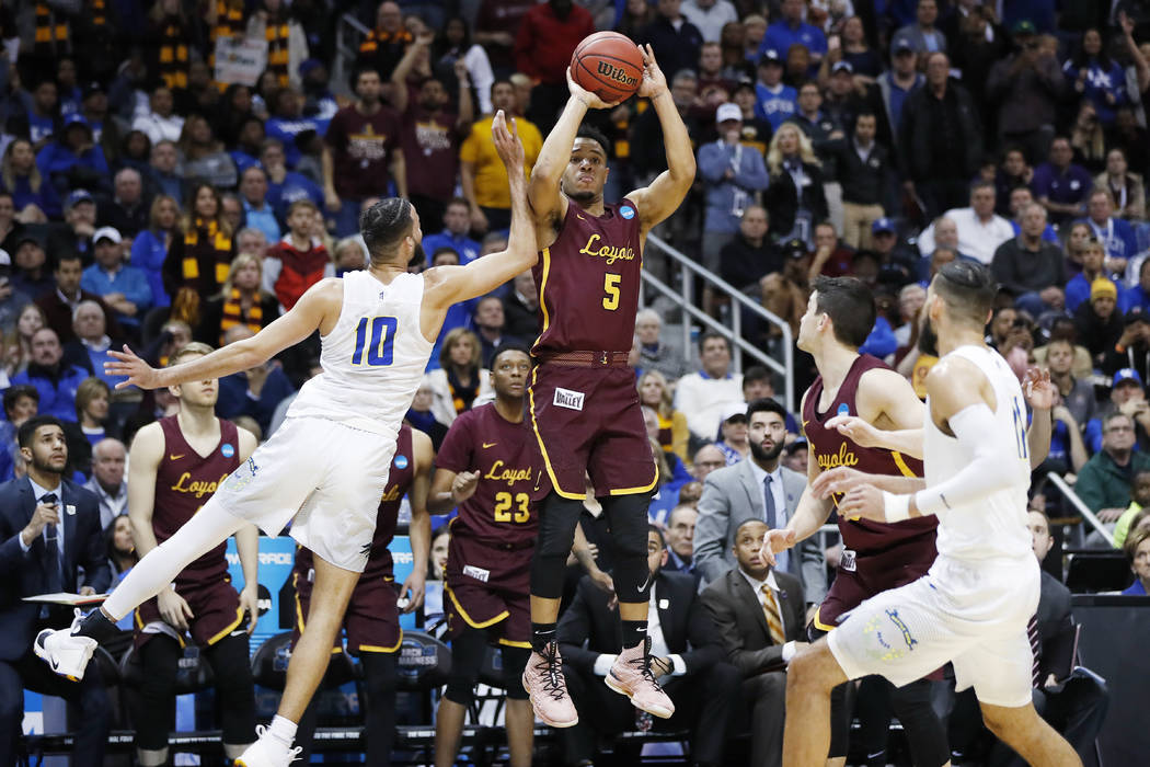 Loyola-Chicago guard Marques Townes (5) makes a three-point shot against Nevada forward Caleb Martin (10) late in the second half of a regional semifinal NCAA college basketball game, Thursday, Ma ...