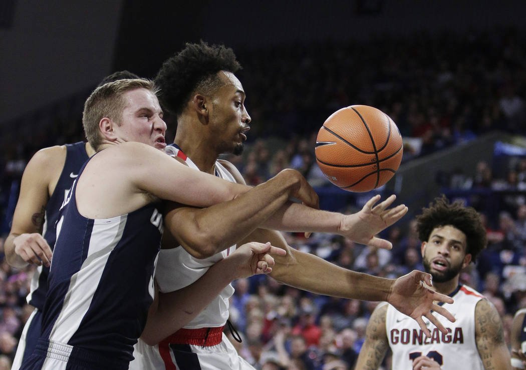 Utah State guard Sam Merrill, left, and Gonzaga forward Johnathan Williams go after a rebound during the first half of an NCAA college basketball game in Spokane, Wash., Saturday, Nov. 18, 2017. ( ...