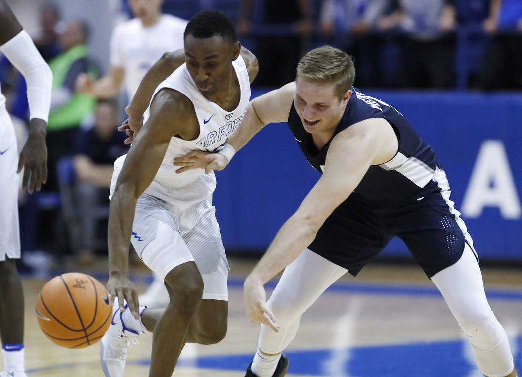 Air Force guard CJ Siples, left, knocks the ball away from Utah State guard Sam Merrill in the second half of an NCAA college basketball game Saturday, Feb. 24, 2018, at Air Force Academy, Colo. ( ...