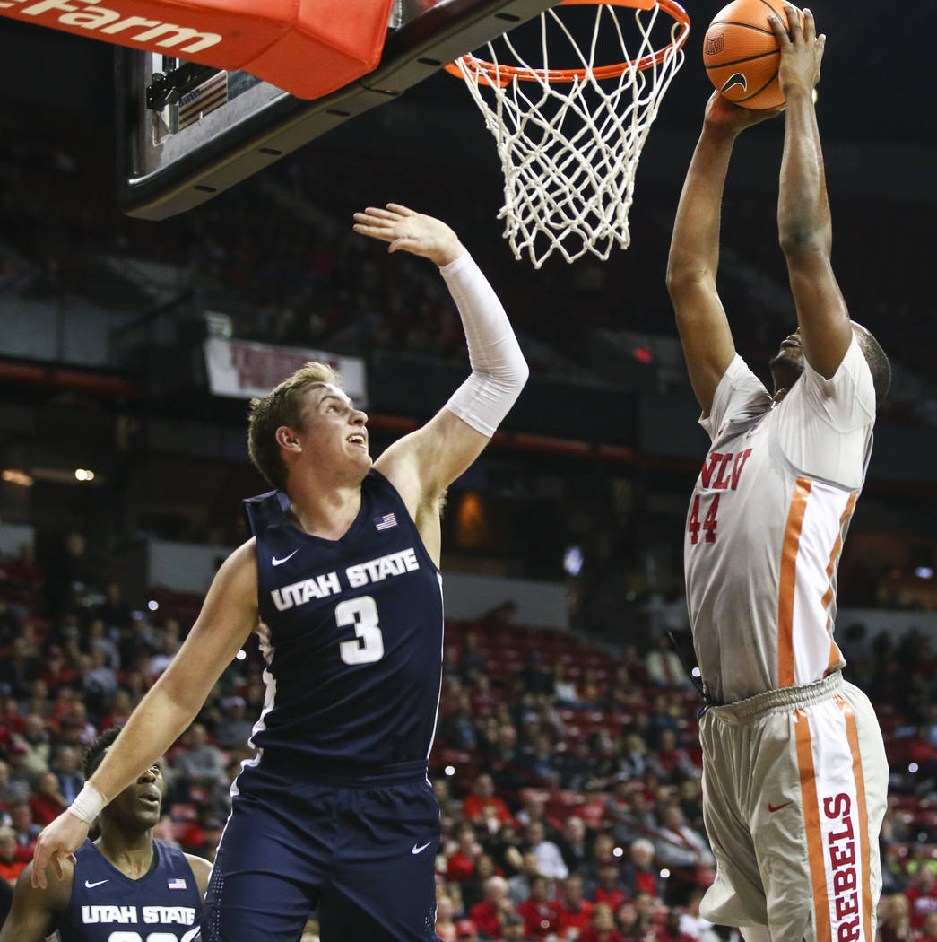 UNLV Rebels forward Brandon McCoy (44) goes up to dunk against Utah State Aggies guard Sam Merrill (3) during the first half of a basketball game at the Thomas & Mack Center in Las Vegas on Sa ...