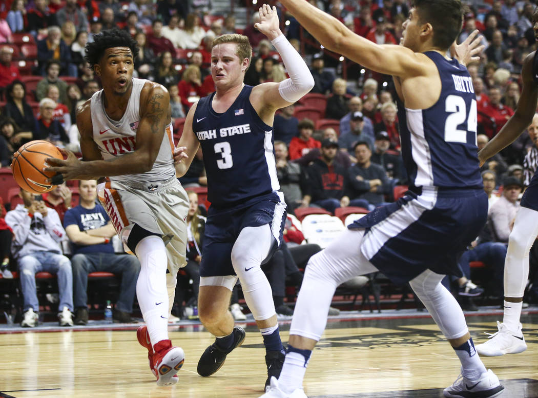 UNLV Rebels guard Jovan Mooring (30) looks to pass as Utah State Aggies guards Sam Merrill (3) and Diogo Brito (24) defend during the first half of a basketball game at the Thomas & Mack Cente ...