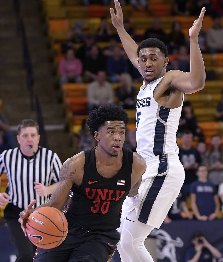 UNLV guard Jovan Mooring (30) works his way past Utah State guard Julion Pearre (5) during an NCAA college basketball game Saturday, March 3, 2018, in Logan, Utah. (Eli Lucero/The Herald Journal v ...