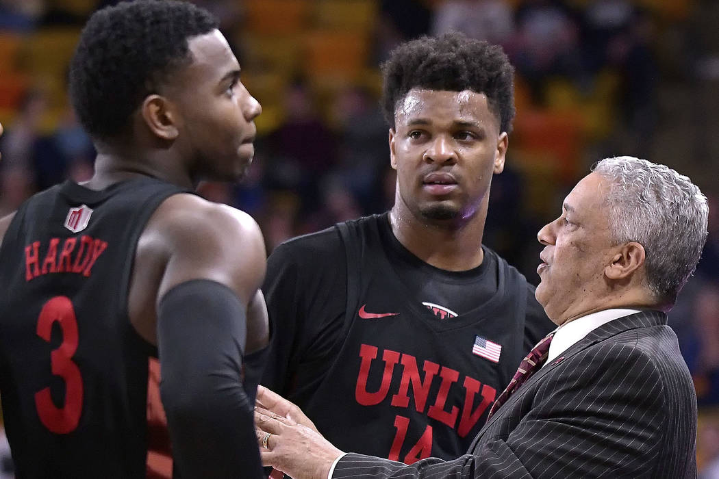 UNLV coach Marvin Menzies talks to guard Amauri Hardy (3) and forward Tervell Beck (14) during a timeout in the team's NCAA basketball game against Utah State on Saturday, March 3, 2018, in Logan, ...