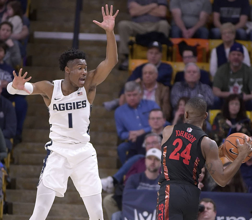 UNLV guard Jordan Johnson (24) looks to pass the ball as Utah State guard Koby McEwen (1) defends during an NCAA college basketball game Saturday, March 3, 2018, in Logan, Utah. (Eli Lucero/The He ...