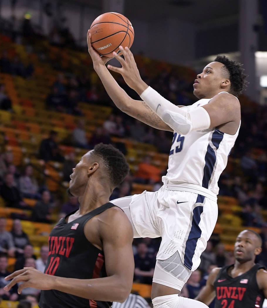 Utah State forward Dwayne Brown Jr. (25) drives to the basket as UNLV forward Shakur Juiston (10) and guard Jordan Johnson (24) defend during an NCAA college basketball game Saturday, March 3, 201 ...