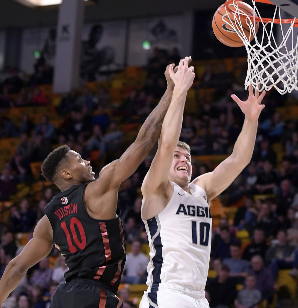 Utah State forward Quinn Taylor, right, shoots as UNLV forward Shakur Juiston defends during an NCAA college basketball game Saturday, March 3, 2018, in Logan, Utah. (Eli Lucero/The Herald Journal ...