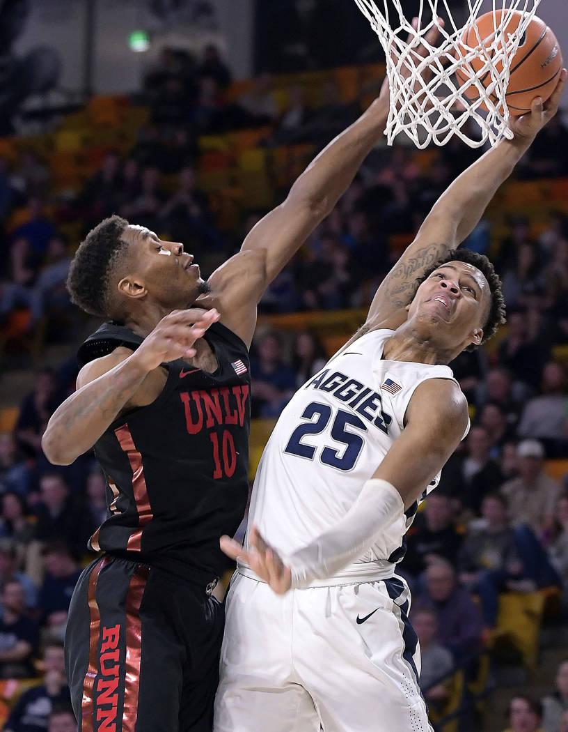 Utah State forward Dwayne Brown Jr. (25) drives to the basket as UNLV forward Shakur Juiston (10) defends during an NCAA college basketball game Saturday, March 3, 2018, in Logan, Utah. (Eli Lucer ...