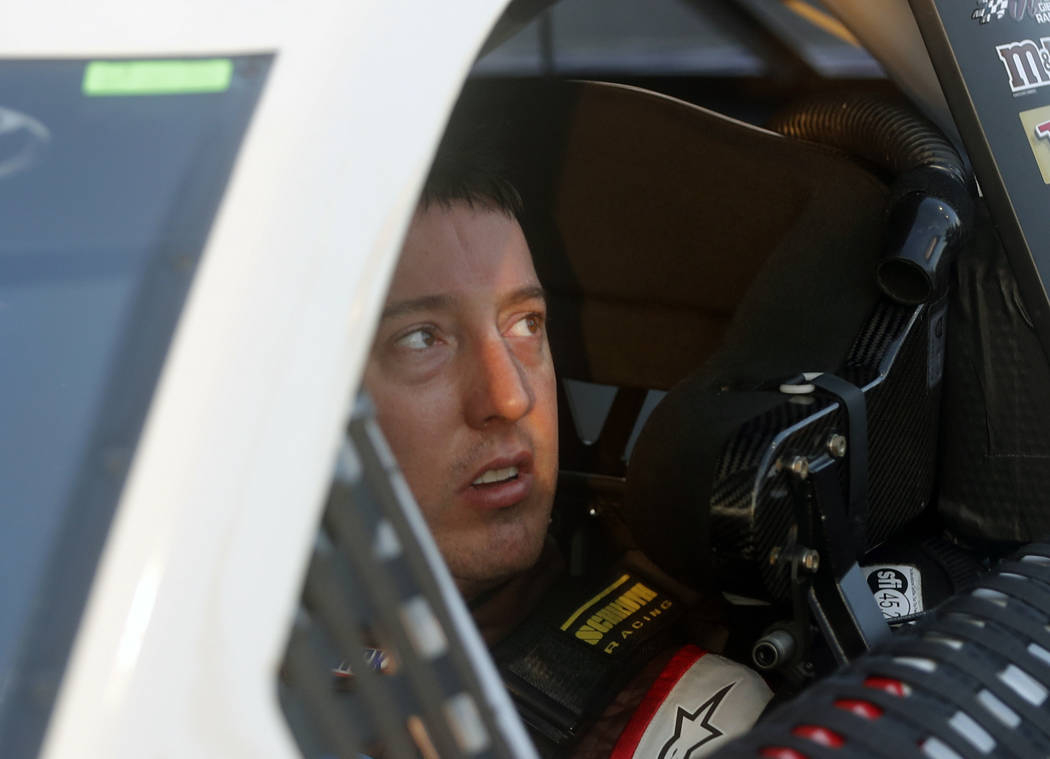 Kyle Busch sits in his car after winning the pole for Sunday's NASCAR Cup series auto race at Atlanta Motor Speedway in Hampton, Ga., Friday, Feb. 23, 2018. (AP Photo/John Bazemore)
