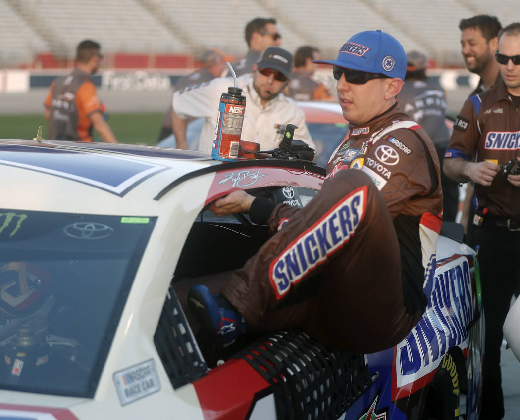 Kyle Busch climbs out of his car after winning the pole for Sunday's NASCAR Cup series auto race at Atlanta Motor Speedway in Hampton, Ga., Friday, Feb. 23, 2018. (AP Photo/John Bazemore)