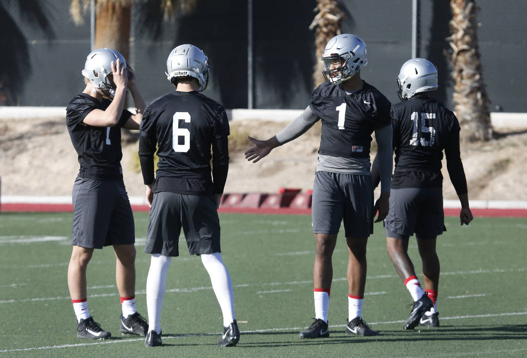 UNLV quarterbacks Kenyon Oblad, left, Armani Rogers (1), Marckell Grayson (15) and Max Gilliam (6) take a break during the first day of spring practice on Tuesday, March 6, 2018, in Las Vegas. Biz ...