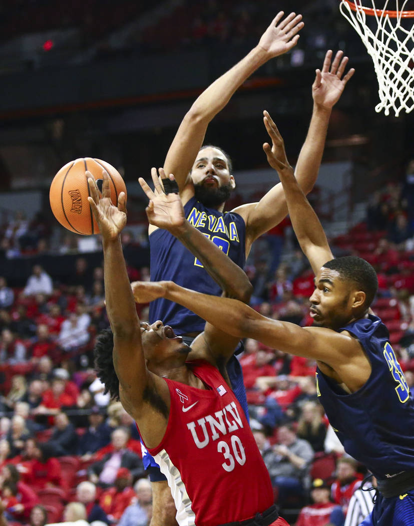 UNLV guard Jovan Mooring (30) gets blocked by UNR guard Josh Hall (33) and forward Caleb Martin (10) during the second half of a basketball game at the Thomas & Mack Center in Las Vegas on Wed ...