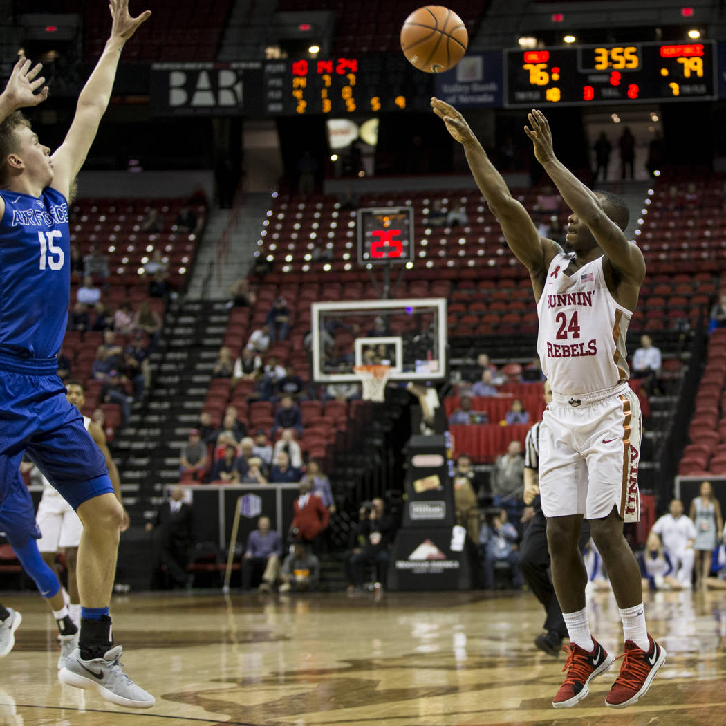 UNLV Rebels guard Jordan Johnson (24) shoots a three-point shot for a score with pressure from Air Force Falcons guard Jacob Van (15) during overtime in the Mountain West Conference men's basketba ...