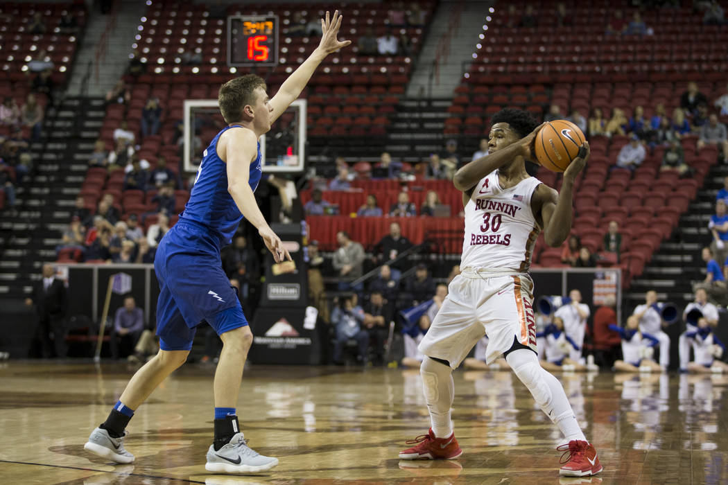 UNLV Rebels guard Jovan Mooring (30) looks for an open pass under pressure from Air Force Falcons guard Jacob Van (15) during overtime in the Mountain West Conference men's basketball tournament g ...