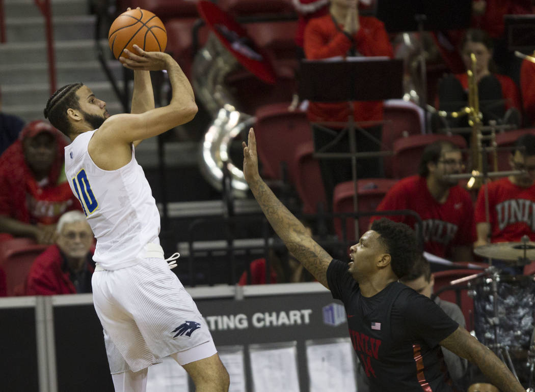 Nevada Wolf Pack forward Caleb Martin (10) takes a shot under pressure from UNLV Rebels forward Tervell Beck (14) in the first half of the Mountain West Conference men's basketball tournament game ...