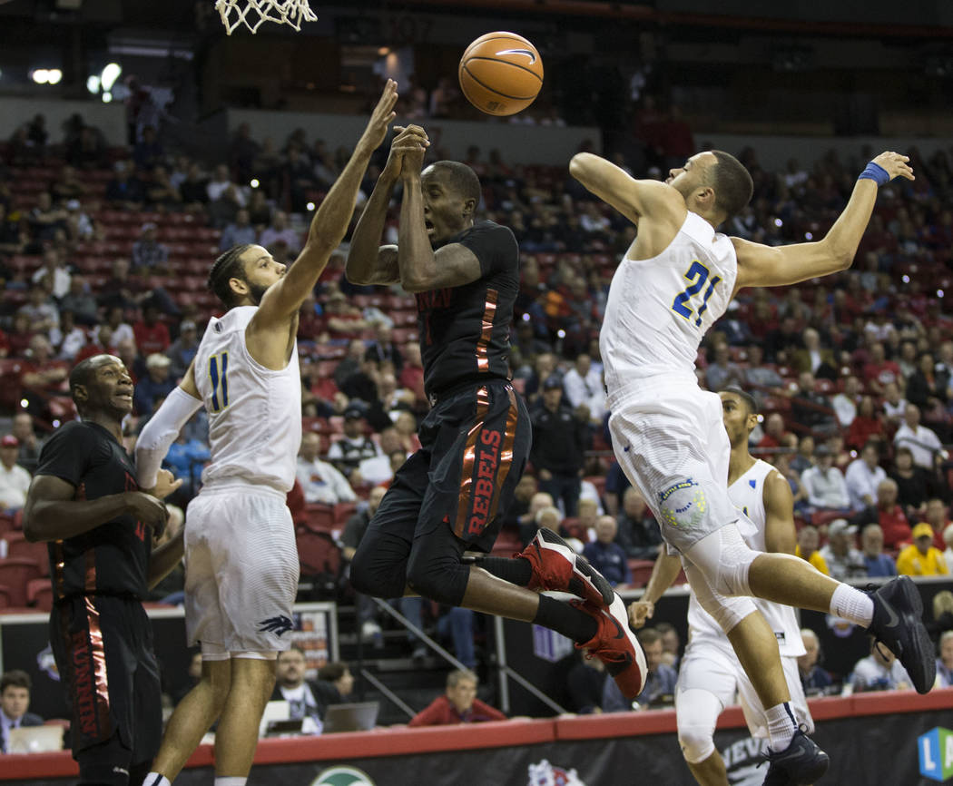 UNLV Rebels guard Kris Clyburn (1) is blocked by Nevada Wolf Pack guard Kendall Stephens (21) in the first half of the Mountain West Conference men's basketball tournament game at the Thomas & ...