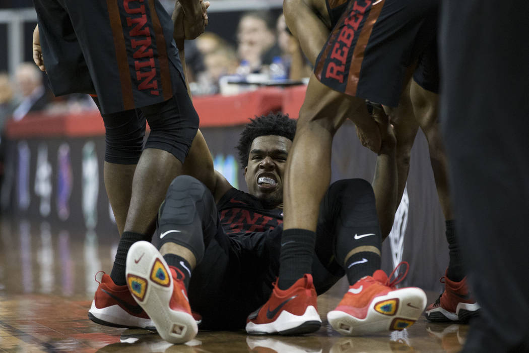 UNLV Rebels guard Jovan Mooring (30) is assisted off the floor after taking a foul in the second half of the Mountain West Conference men's basketball tournament game at the Thomas & Mack Cent ...